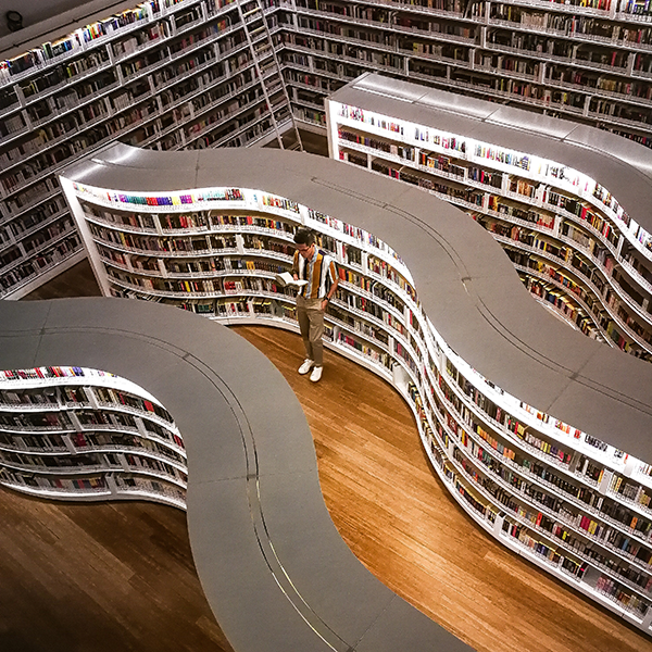 Aerial image of person in library with curvy rows of books