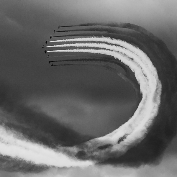 Grayscale image of jets flying in unison with smokescreen