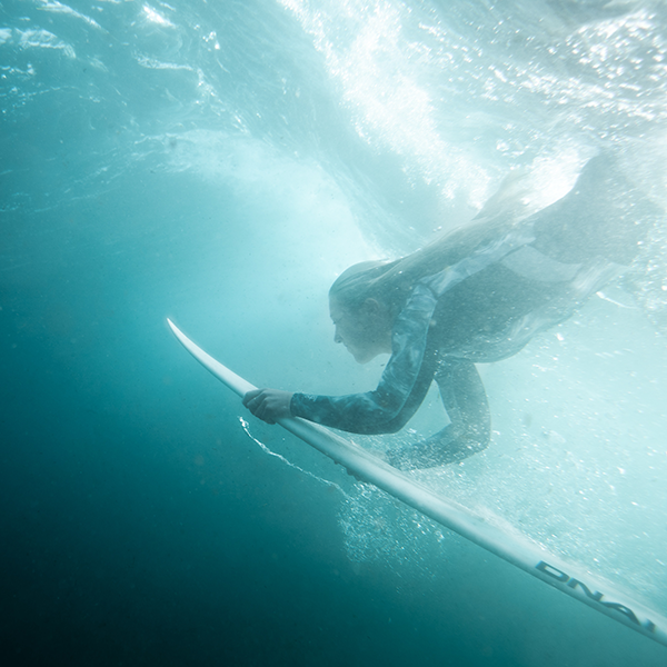 Surfer duck diving under wave with surfboard