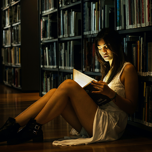 Figure sitting on floor of library row reading in the dark